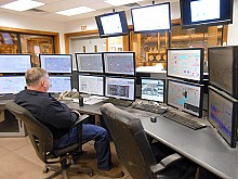 An employee oversees plant operations via a big bank of computers in the control room. Photo: Joanna Richards