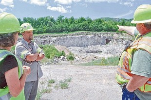 Brett Lawson, superintendent at NYCO Minerals' Lewis mine, points in June 2013 toward a 200-acre parcel of state-owned land, above and behind the rock wall, where the company wants to mine wollastonite. Also pictured, from left, are NYCO employees Dawn Revette and Brian Shutts. Photo by Chris Knight, Adirondack Daily Enterprise