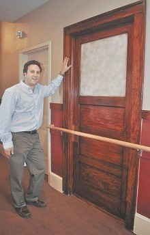 "Eli Schwartzberg, owner and developer of the Champlain Valley Senior Community, stands next to one of the old doors from the Willsboro Central School, several of which were preserved during the extensive renovations of the building. Photo: Chris Knight, via <a href=""http://www.adirondackdailyenterprise.com/page/content.detail/id/537874/Converted-school-fills-void-for-seniors.html"">Adirondack Daily Enterprise</a>"
