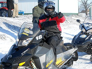 The governor goofs with reporters from his snowmobile. Photo: Joanna Richards