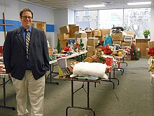 Watertown Urban Mission Development Director Drew Mangione stands amid tables full of Christmas decorations, for sale at affordable prices through December 15. Photo: Joanna Richards
