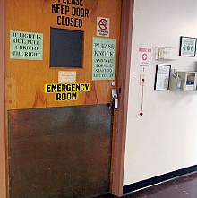 A sign on the door to the emergency room at Clifton-Fine Hospital tells people to pull the cord if the light is off. Photo: Julie Grant
