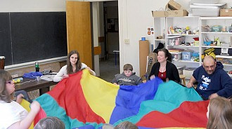 Tracy Wannamaker (second from the right) says parachute play is used to add an exciting element to singing games and movement activities during the class. Photo: Todd Moe