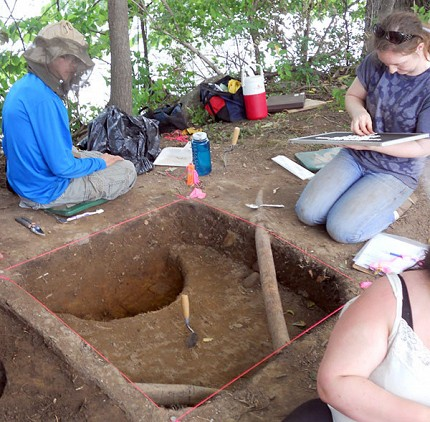 Students Cooper Sheldon and Emmaline Voss at one of the dig sites along the Raquette River in Potsdam. They examine bits of prehistoric pottery and animal bones found at the site. Photo: Todd Moe