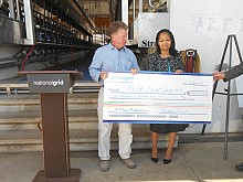 National Grid Regional Executive of Central New York Melanie Littlejohn presents farmer John Ferry with a symbolic check in his milking facility. Photo: Joanna Richards