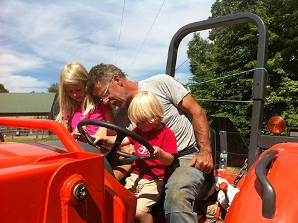 Bill Knoble and grandchildren on the tractor.