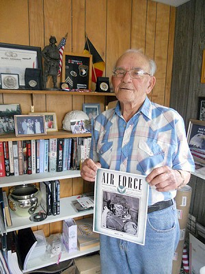 Bob Noody in the study at his Star Lake home.  He holds a copy of the Air Force magazine from 1944 that used his photo on the cover.  Photo: Todd Moe