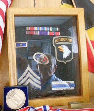 Bob Noody reflected in a framed collection of medals, badges and uniform patches from World War II.  Photo: Todd Moe