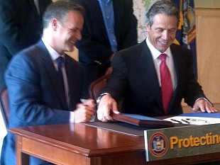 Gov. Andrew Cuomo with Bill Ulfelder, Executive Director of the Nature Conservancy in New York, signing the Finch Pruyn deal in Lake Placid. NCPR Photo: Brian Mann