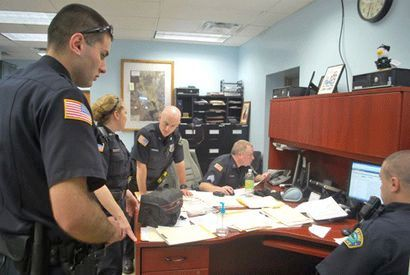 Members of the Saranac Lake Police Department discuss the progress a series of drug raids around the village. From left are Patrolman Aaron Donaldson, Patrolwoman Reyanin Peck, Patrolman James Joyce, Sgt. Bill Cote and Patrolman Jason Swain. Photo:  Chris Knight, courtesy <em>Adirondack Daily Enterprise</em>