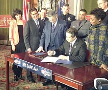 Governor Cuomo signs the SAFE Act. Photo: Karen DeWitt