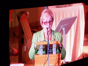 Mayor Colette Roy-Laroche speaks at St. Agnes church early Sunday morning, her image projected on a large-screen TV outside.  Photo:  Brian Mann