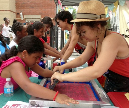 "Milk Not Jails tries to spread its message with fun, too. MNJ volunteers help kids make silkscreen posters that read ""Pop the Prison."" Photo: David Sommerstein"