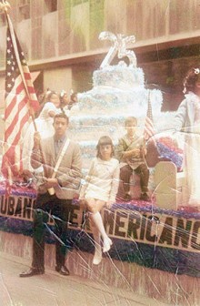 George Prendes (holding the flag) with his younger sister Mercedes and younger brother Roberto, at a Cuban American parade.