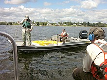 Scientists bring buckets of lampricide to the treatment boat. Photo: Sarah Harris