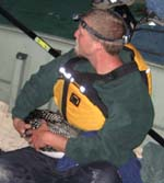 DEC wildlife technician holds a male loon captured on Garnet Lake