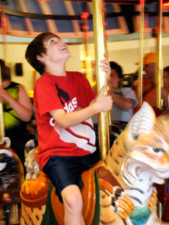 Checking out the mechanicals overhead on the Adirondack Carousel as it spins on one of the inaugural rides. Photo: Mark Kurtz