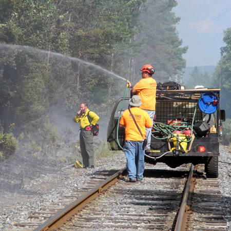 Crews containing a forest fire along the tracks between Lake Placid and Saranac Lake last summer. Photo: <em>Adirondack Daily Enterprise</em>