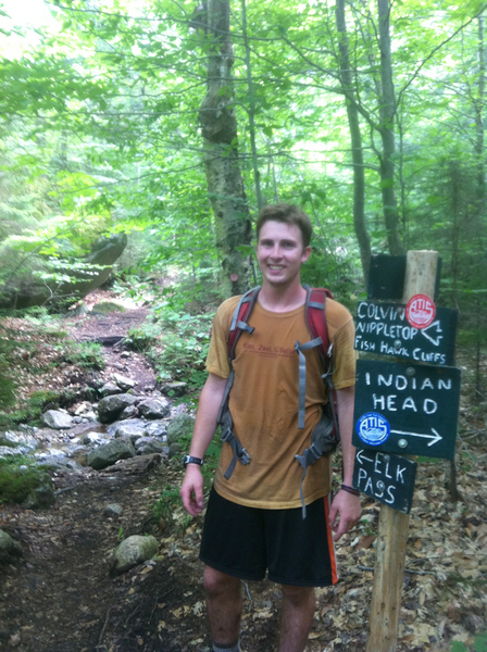 Conant stands near a sign at a trail convergence. Photo: Phil Duggan
