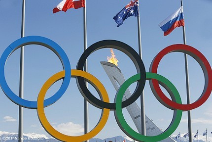 Rings and national flags in the foreground, the Olympic flame and the snowcapped mountains behind. Photo: © Nancie Battaglia