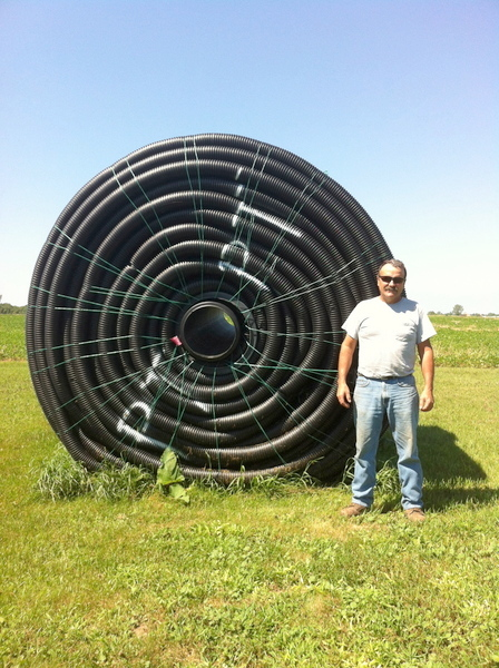 Guy Palardy in front of a roll of drainage pipe. Photo: Sarah Harris.