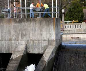 Saranac Lake Village workers last week, working on closing one of the gates after releasing some water. Photo: Mark Kurtz
