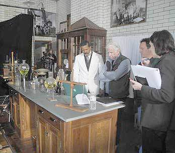A film crew from Maryland-based Signature Communications prepares to shoot scenes for a film about George Washington Carver in Historic Saranac Lake's Trudeau Laboratory on Church Street Wednesday. The actor in the white suit playing Carver is Altorro Black. Standing to his left is the film's producer, John Allen.<br />(Adirondack Daily Enterprise photo -- Chris Knight)<br />