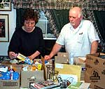 Gladys and John Walker sort through boxes of supplies bound for the Middle East