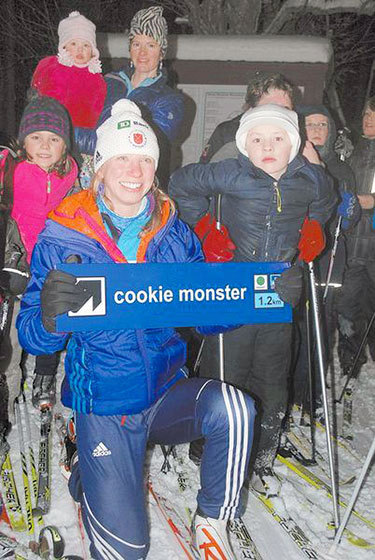 Surrounded by children in the Dewey Mountain Recreation Center youth ski program, biathlete Annelies Cook of Saranac Lake holds a sign for a trail at the ski center named for her Thursday. Cook was nominated this month to the U.S. Olympic Team for February's winter games in Sochi, Russia.  Photo: Chris Knight, courtesy of <em>Adirondack Daily Enterprise</em>