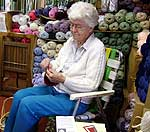 Annis knits up to six hours a day in her Chestertown yarn shop (above), and models a pair of Adirondack Buff mittens (below)