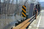 A transportation worker clears debris from a bridge over the East Branch of the Ausable River near Keene.