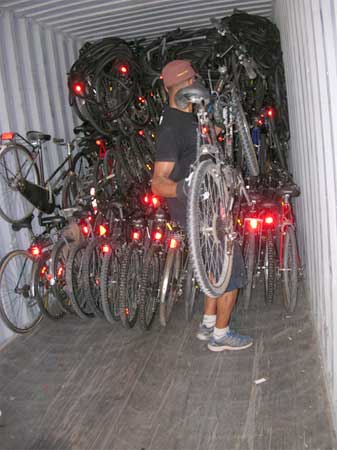 A volunteer stacks the bikes into a pile at the back of a huge shipping container. Photo: Karen Kelly