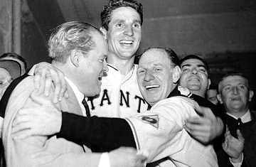 New York Giants baseball player Bobby Thomson, center, being hugged by Giants owner Horace Stoneham and manager Leo Durocher.