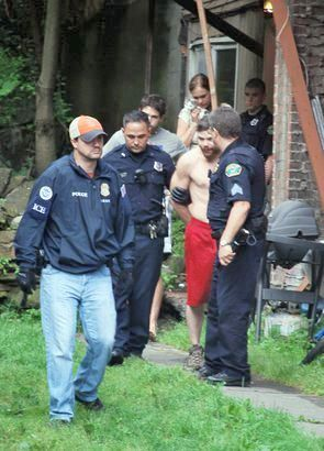 Police take a suspect into custody as part of a drug sweep in Saranac Lake.  This strategy has been used for decades to reduce drug-related crime in the North Country. Photo: Chris Knight