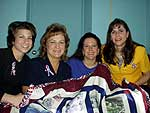 Family Readiness coordinators show off the I-87 battalion quilt.  L-R, Heather Taylor, Kathy Koop, Denise Cornell, and Theresa LaCamera.