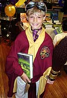 11-year-old Hans Kuno, of Hannawa Falls (above), in his quidditch uniform, joined other fans at the Brewer Bookstore in Canton.  He dove into the book after buying it Saturday. (below)
