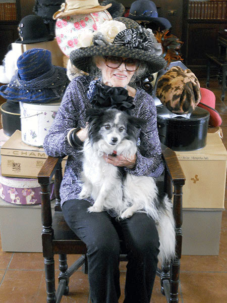 Ursula Trudeau and Max pose wearing favorite hats surrounded by dozens of others at the Saranac Laboratory in Saranac Lake.  Photo:  Todd Moe