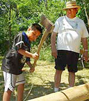 Chief Jake Swamp looks on while his grandson, Frank, hammers a log to loosen strips for basketmaking.