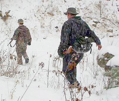 John and Brenan Quinn head back to camp. The prize of the hunt is a buck, but many hunters say the real goal is spending time in the woods with family. Photo: Brian Mann, 2002