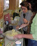 Martha Foley & Ellen Rocco mix the latke batter.  Below, latkes on the griddle!!