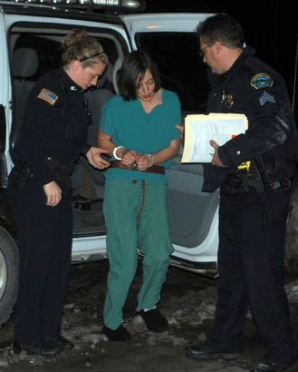 Saranac Lake police officers help Angela Ball out of a police car on her way into the Harrietstown Town Hall courtroom for arraignment on a second-degree murder charge Monday night in Saranac Lake. Photo: Chris Knight, Adirondack Daily Enterprise