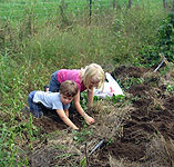 Young gardeners Syl and Sage hunt for potatoes in the Cecilie Garden