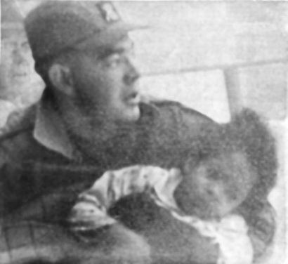 Saranac Lake firefighter Preston Burl carries 4-year-old Ruth King after rescuing her from a fire that destroyed the St. Regis Hotel on Jan. 14, 1964. Photo: <em>Adirondack Daily Enterprise</em>