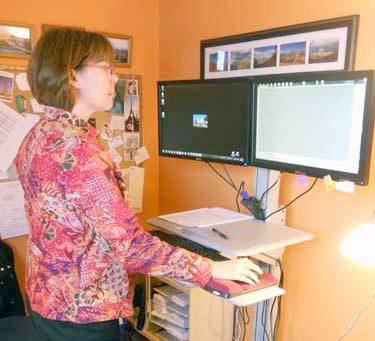 St. Lawrence Health Initiative Exec. Director Ruth Fishbeck says all 13 of her employees have similar standing desks in their offices. Photo: Todd Moe