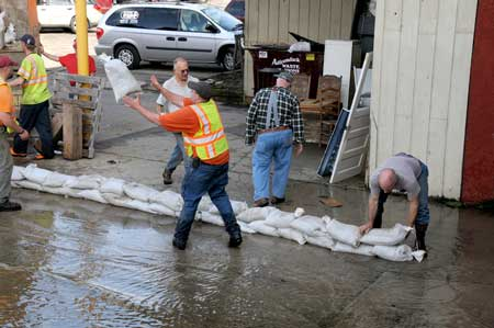 Sandbagging along the Saranac River below the Broadway bridge. Photos: Mark Kurtz.