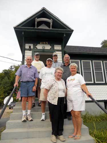 Some of the members of the Save our School committee on the front steps of the restored schoolhouse in Star Lake. Photo: Todd Moe