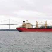 A Seaway freighter passes under the bridge near Massena in December 2012.  Photo: David Sommerstein.