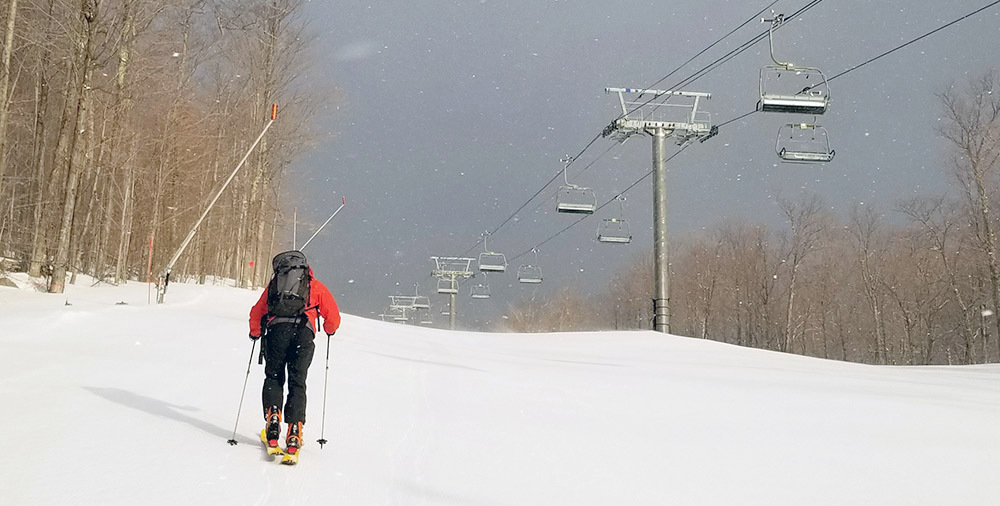 Aaron Woolf trudges uphill toward the summit of Little Whiteface. Photo: Brian Mann